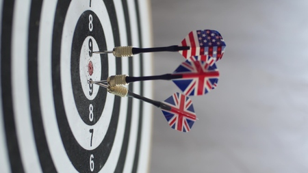 Close up of darts hitting the bulls eye on a dartboard Concept of successful business ideas hitting the exact center of the target. Perfect performance of the task and superiority over the rivals