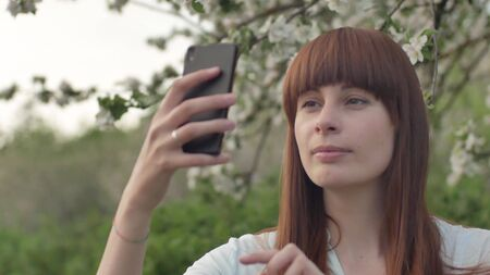 Girl makes selfie in the garden. An attractive red-haired woman smiles making selfi using a mobile phone in a cherry orchard. The concept of using gadgets for a healthy lifestyle.