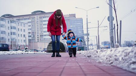A young woman leads a infant by the hands down the street in winter. First steps baby