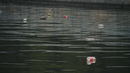 Trash floats in the city canal. Environmental pollution