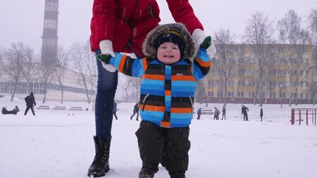 Mother leads the hands of a small smiling baby in the snow in the park. The first steps of the child. Parental care