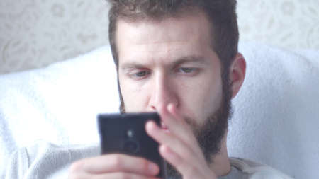 A young bearded man uses his mobile phone. Close-up shot, focus on eyes.