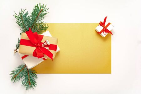 2020 Happy New Year, Merry Christmas decorations flatlay. Gift boxes, red ribbon, spruce branch top view. Boxing Day banner template, gold paper frame, copy space. Xmas concept mock up, greeting card.