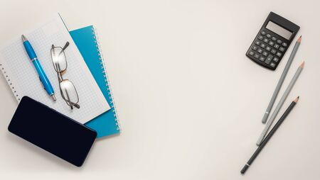 Stay at home white background flatlay. Home office smartphone blue notebook pencils pen top view template long banner. Copy space backdrop mock up design. Distance education creative work concept.