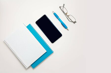 Stay at home white background flatlay. Home office smartphone blue notebook glasses blue pen top view template long banner. Copy space backdrop mock up design. Distance education creative work concept Foto de archivo