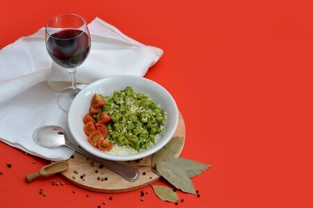 spinage: Glass of red wine and plate of spaghetti on red background