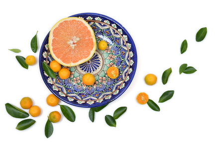 citrons: Cut grapefruit and citrons on old vintage painted plate on a white background with scattered leaves