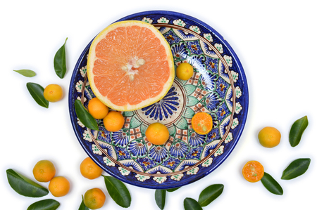 citrons: Grapefruit and citrons on old vintage painted plate on a white background with scattered leaves. Closeup. Top view.