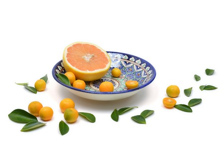 citrons: Cut grapefruit and citrons on old vintage painted plate isolated on white background with scattered leaves. Composition with grapefruit and citrus leaves