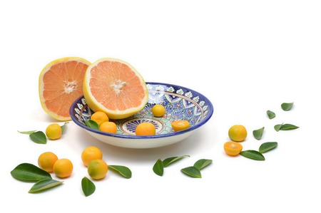 citrons: Cut grapefruit and citrons on old vintage painted plate isolated on white background with scattered leaves. Composition with grapefruit sliced in half and citrus leaves