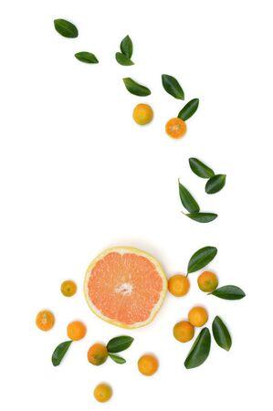 pomelo: Corte el pomelo rodeados de hojas y pequeñas mandarinas aislados en blanco. Vista superior de pomelo con mandarinas y hojas.