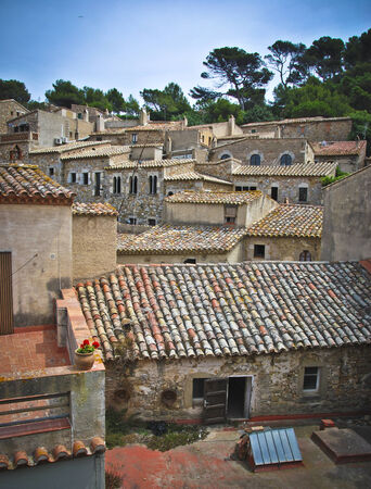 spanish houses: Tiled roofs of ancient spanish houses built in tiers on the side of a hill Stock Photo