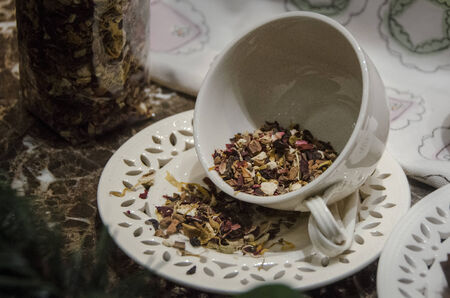Tea cup and saucer with herbal tea leaves photo