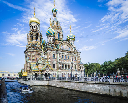 Russian church with coloured onion domes and a boat on the canal in the foreground