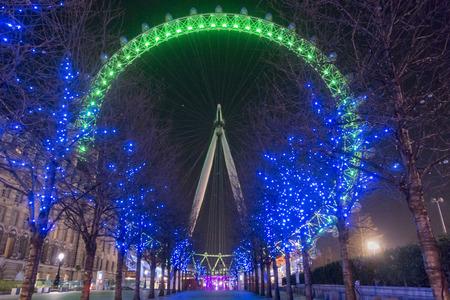 london eye: London eye in green and avenue of blue lit trees