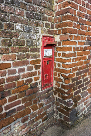 red post box: Red post box in a brick wall Stock Photo