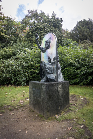lewis carroll: Statue depicting Alice through the looking glass in public park, Guildford, Surrey, Great Britain
