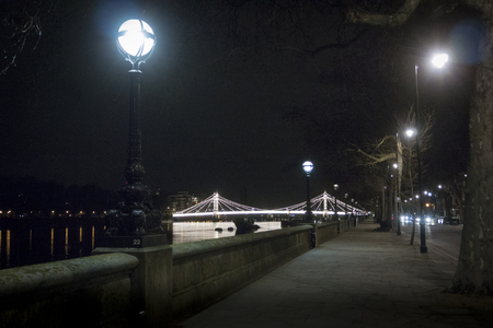 chelsea: The embankment of the River Thames at night with Chelsea bridge lit up in the background