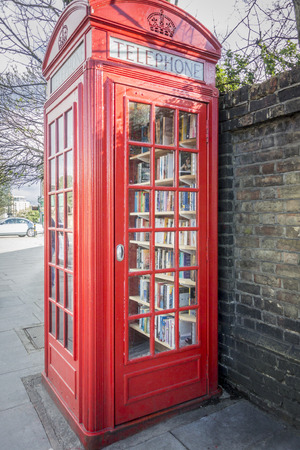 antique booth: British red telephone box now used as a micro library Stock Photo