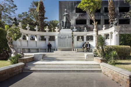 egypt revolution: CAIRO, EGYPT, 05 JANUARY 2015 - Tomb and statue of Auguste Mariette (a 19th century French egyptologist), in the grounds of Cairo Museum, with a government building destroyed during the Egyptian Revolution of January 2011 in the background and Egyptian me
