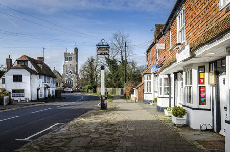 kent: BIDDENDEN, Kent, UK, JANUARY 2015 - High street with cobbled pavement, historic buildings and church in the background Editorial