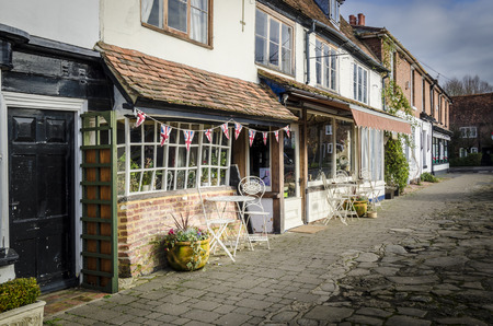 Old village High Street with tea rooms in the foreground Stock Photo