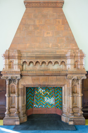 mantelpiece: Ornate, old red bricked fireplace no longer in use