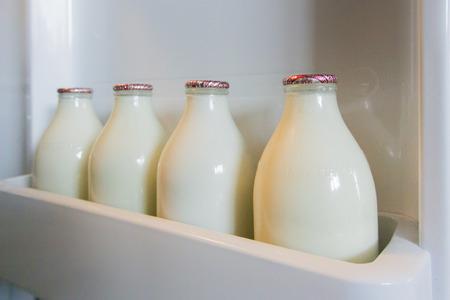 milk milk products: Paisaje imagen de cuatro botellas de leche de vidrio en un estante de la puerta nevera Foto de archivo