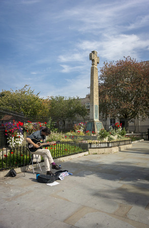 memorial cross: 28 de septiembre 2014, Glastonbury, Somerset, Reino Unido - Busker tocando la guitarra junto a la cruz conmemorativa celta en la calle Mayor, Glastonbury Editorial
