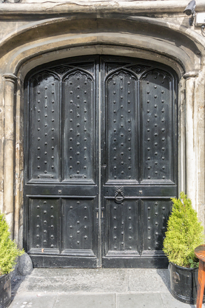 surround: Medieval wooden studded double door with ancient stone surround