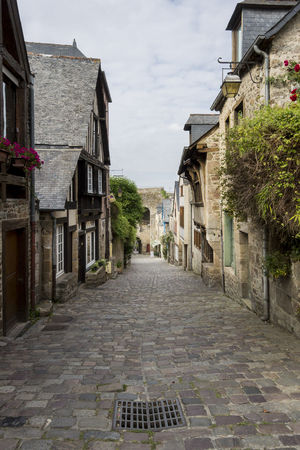 dinan: Downward view of a cobbled street in Dinan, Brittany, France with medieval houses either side, in portrait format