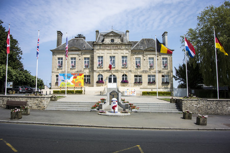 mere: Town hall of St Mere Eglise, Normandy France with a liberation marker in front of the towns war memorial