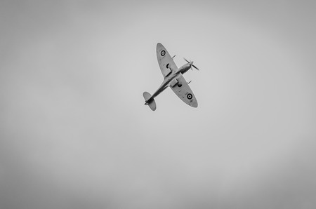 undercarriage: HEADCORN, KENT, ENGLAND - 15 AUGUST 2015: The undercarriage of a lone Spitfire aeroplane in flight in greyscale