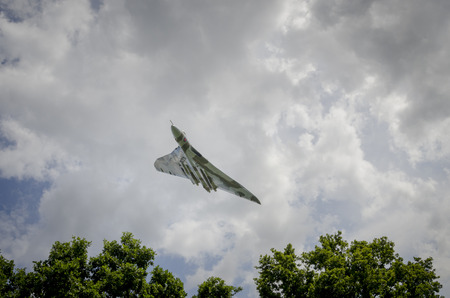 treetops: HEADCORN, KENT, ENGLAND - 15 AUGUST 2015: Avro Vulcan XH558 circles the Kent countryside on August 15, 2015 The V-Force Tour. XH558 Avro Vulcan was the worlds last flying Vulcan. Editorial