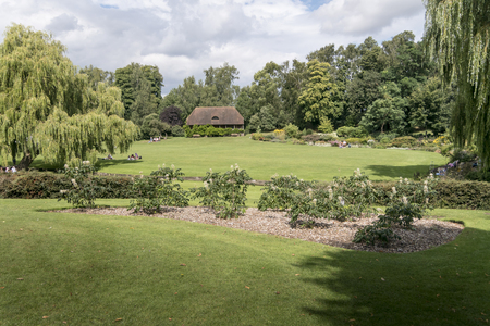 picnicking: LEEDS CASTLE GARDENS, KENT, UK, 21 AUGUST 2015 - Gardens of Leeds Castle with a cottage in the distance and people picnicking on the lawn