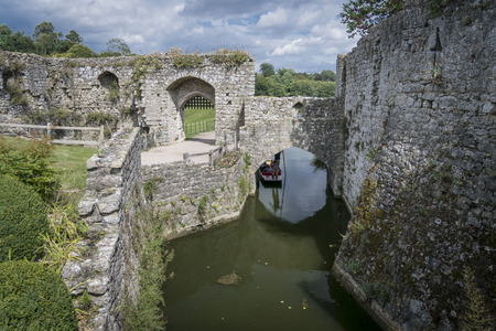 moat wall: LEEDS CASTLE, KENT, UK, 21 AUGUST 2015 - Leeds Castle moat with a punt about to go under the arch Editorial