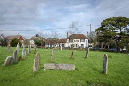 public house: WOODCHURCH, KENT, UK, 25 JANUARY 2016 - All Saints graveyard with the Bonny Cravat public house in the background in the village of Woodchurch, Kent, UK