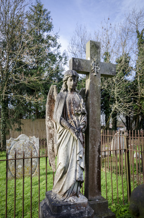 angel headstone: An ornate headstone of an angel in a church graveyard