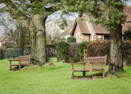 kent: Benches under trees in the village of Woodchurch, Kent, UK