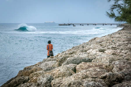 breaking in: Man on the shore watching the waves breaking in the sea on a windy day, at Bridgetown, Barbados