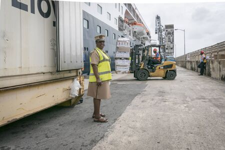 ship lift: BRIDGETOWN, BARBADOS, 21 DECEMBER 2015 - Port staff loadig provisions onto ship by fork lift truck at the cruise terminal, Bridgetown, Barbados Editorial