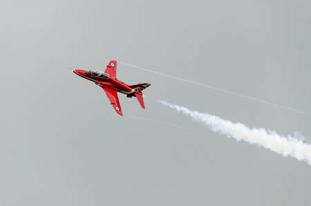 vapour: HEADCORN, KENT, ENGLAND - 15 AUGUST 2015: A single Red Arrow aeroplane in flight with white vapour emitting from its tail end