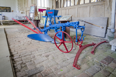 farm equipment: Antique farm equipment, plough on brick floor