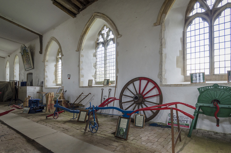 plough machine: Various antique farming equipment on display inside a church Editorial