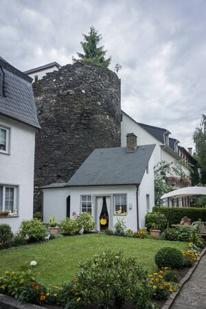 outhouse: Pretty garden and decorated shed with old stone tower behind, in Germany