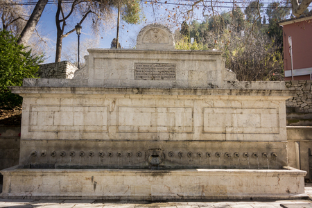 Neo-classical wall fountain with 25 snake shaped pipes.  Wording translates to: 'With my crystal waters I quench the thirst of farmers, the crops grow, populations increase, trade increases and the flowers of Setabis bloom'.  In the city of Xativa (Jativa), Valencia, Spain Foto de archivo