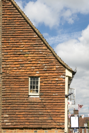 Side view of old house, part gable wall with tiled fascia and georgian window, Battle, Sussex, UK Stock Photo