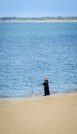 A woman in black, on the beach fishing in the sea