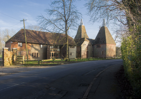 A converted barn and square oast house in a village in Kent, UK