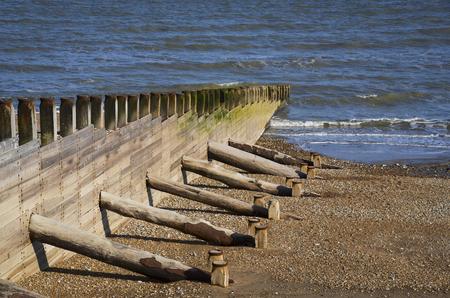A row of groynes on the beach leading to the sea Standard-Bild - 121438206